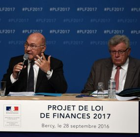 French Finance and Economy Minister Michel Sapin (L) speaks flanked by junior Budget Minister Christian Eckert during a press conference at the Finance and Economy Ministry in Paris on September 28, 2016. / AFP PHOTO / CHRISTOPHE ARCHAMBAULT